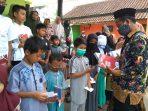 Direktur Yayasan YNGC sedang membagikan mushaf Al Quran kepada anak Yatim Piatu